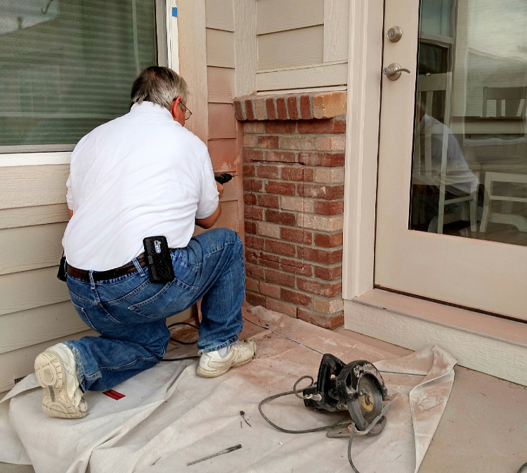 Owner Dan Tripp installing a dog door through brick